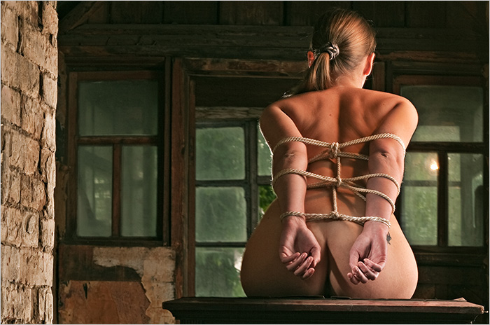 A woman bound with rope around her back in a BDSM domination scene