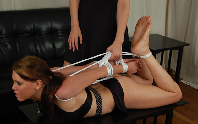 Rope bondage in action: one woman ties another up across a table