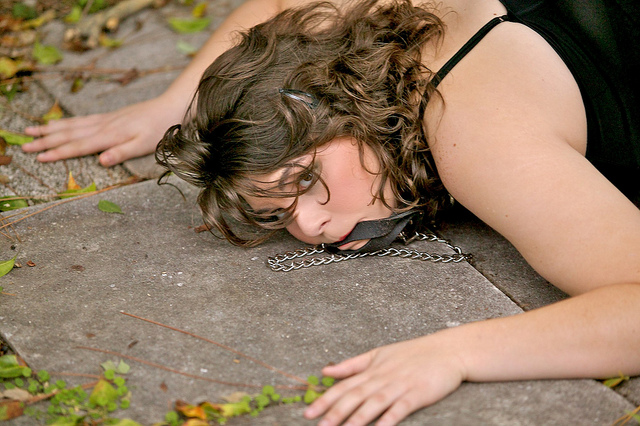 Woman with collar in mouth submits on ground.