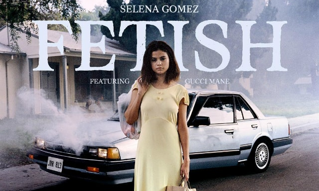 Selena Gomez standing in front of a smoking car carrying shopping bags