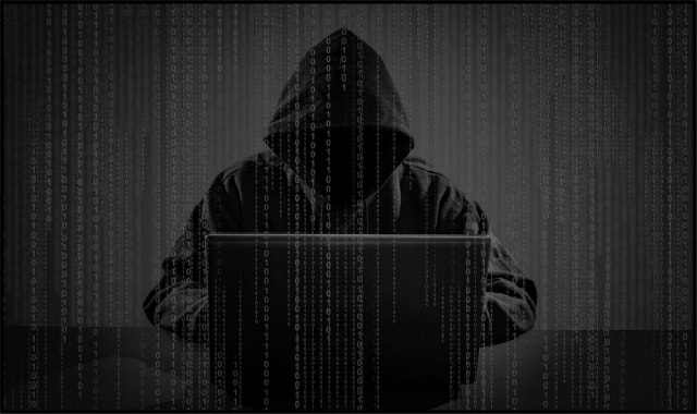 Hacker in black hoodie sitting behind laptop