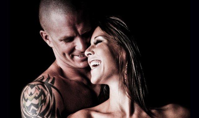 Light BDSM couple laughing together on black background